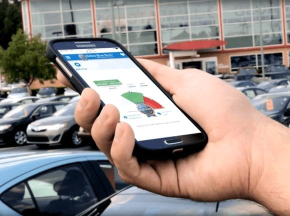 person in a parking lot, looking at Fair Purchase Range on KBB.com