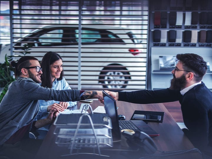 two car buyers shaking hands with dealer while closing a car deal