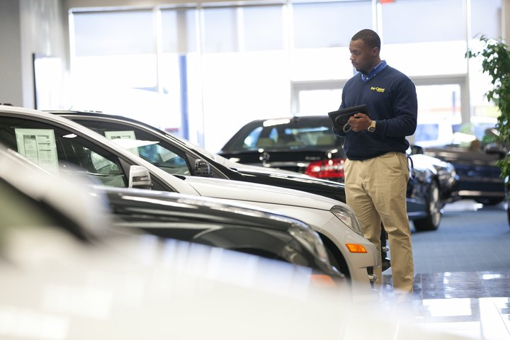 Dealership salesperson looking at a new vehicle on the showroom floor