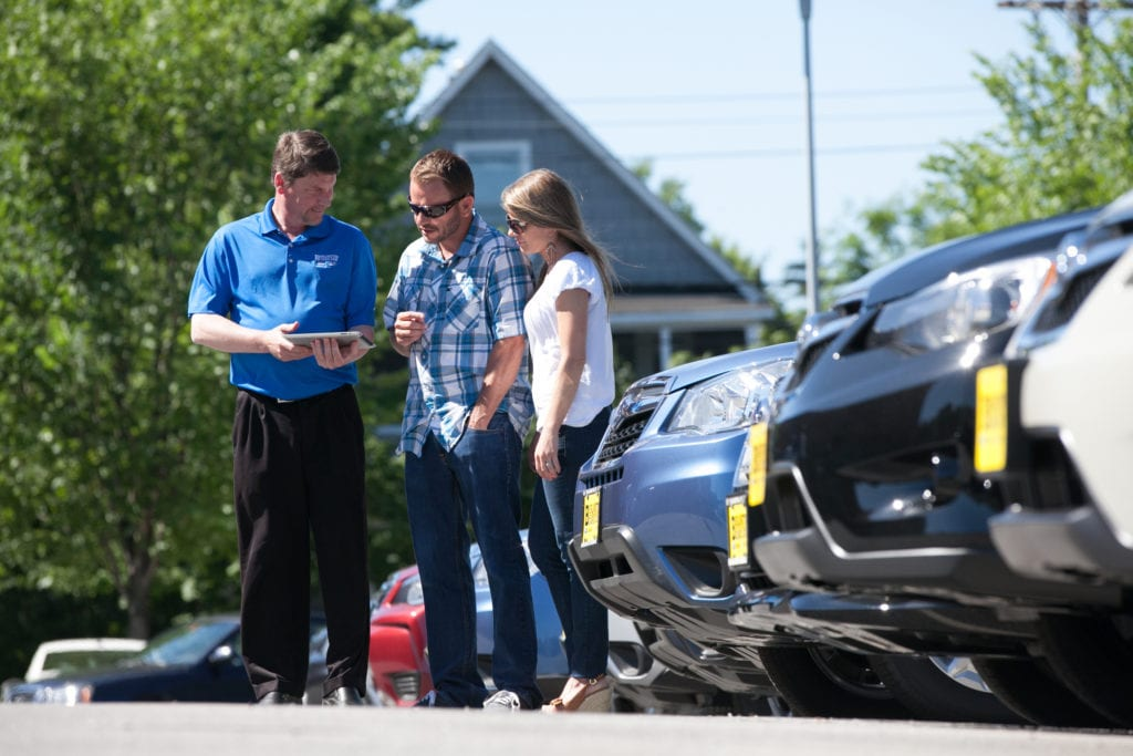 Shoppers with dealer looking for new vehicle