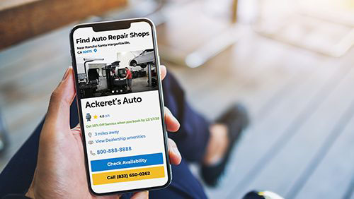 Consumer holding phone with repair shop website